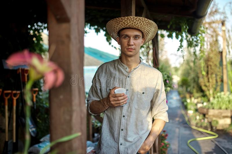 Guy gardener in a straw hat is standing with plastic glass in his hand next to a wooden veranda in the wonderful nursery stock image