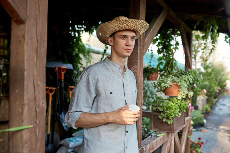 Guy gardener in a straw hat is standing with plastic glass in his hand next to a wooden veranda in the wonderful nursery royalty free stock image