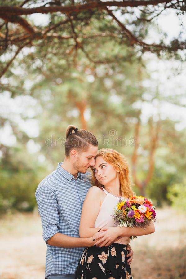 Happy young couple spending time outdoor in the autumn park. The guy gave flowers to a beautiful girl with red hair. stock image
