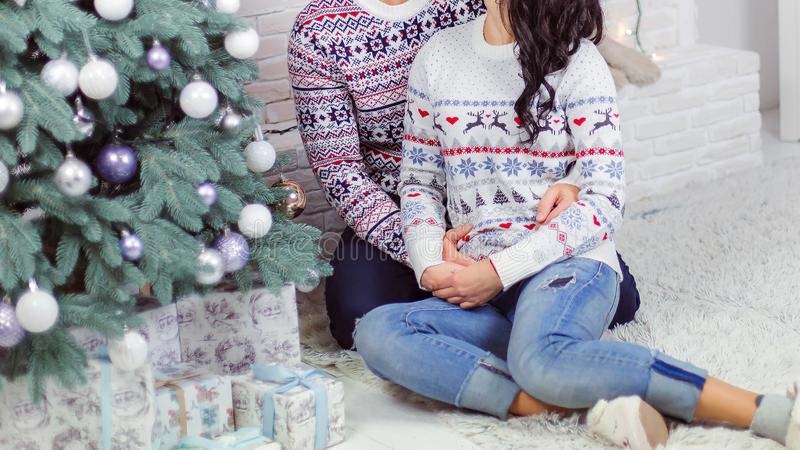 The guy gently hugs a girl near the New Year tree royalty free stock image