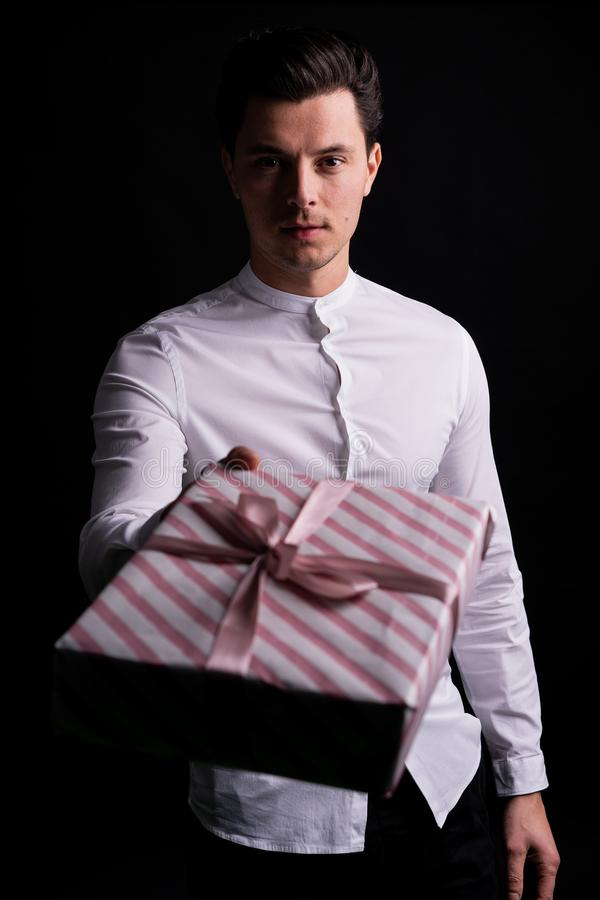 The guy with the gift in his hands. Studio with  black background. The guy gives a gift, and holds it in the camera. Focus on guy stock photos
