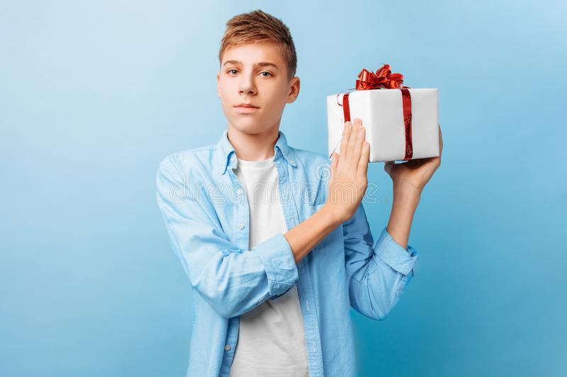 Guy with a gift in his hands for Valentine`s Day, on a light blue background stock photos