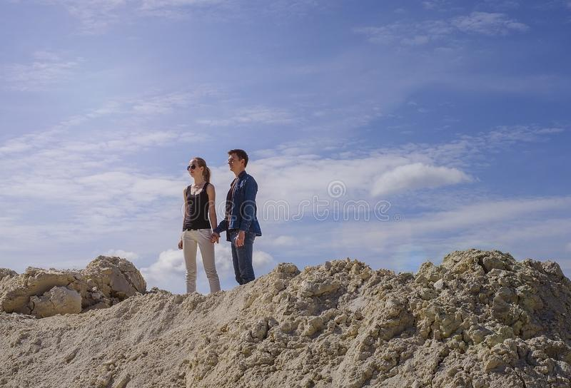 The guy with the girl against the blue sky at the top of the mountain stock images