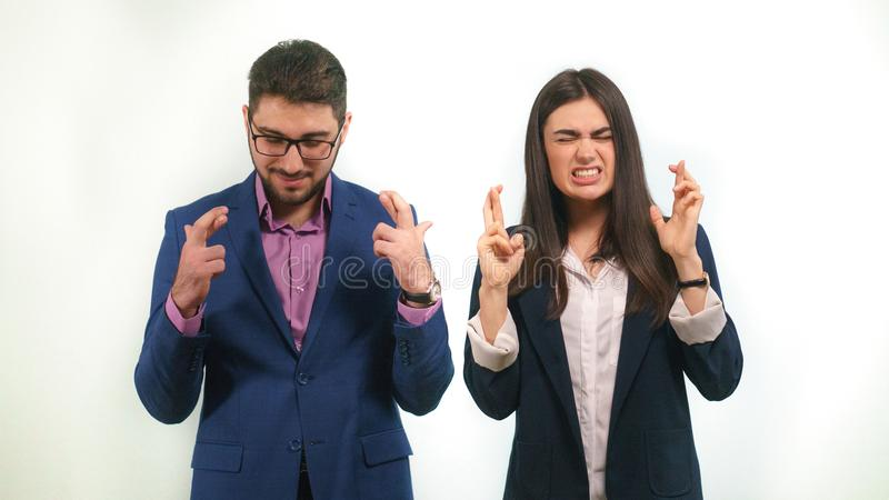 Guy and a girl in business suits crossed their fingers sincerely wishing for the successful project start. Signs attracting good luck interest in the work of royalty free stock photos