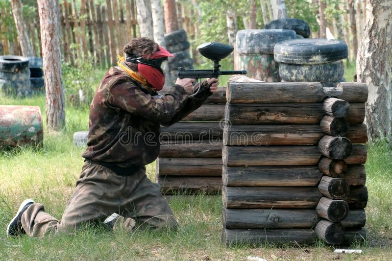 Landfill in the forest for a team game in paintball. A guy or girl in camouflage clothes peeks out from behind a wooden shelter wi stock photography