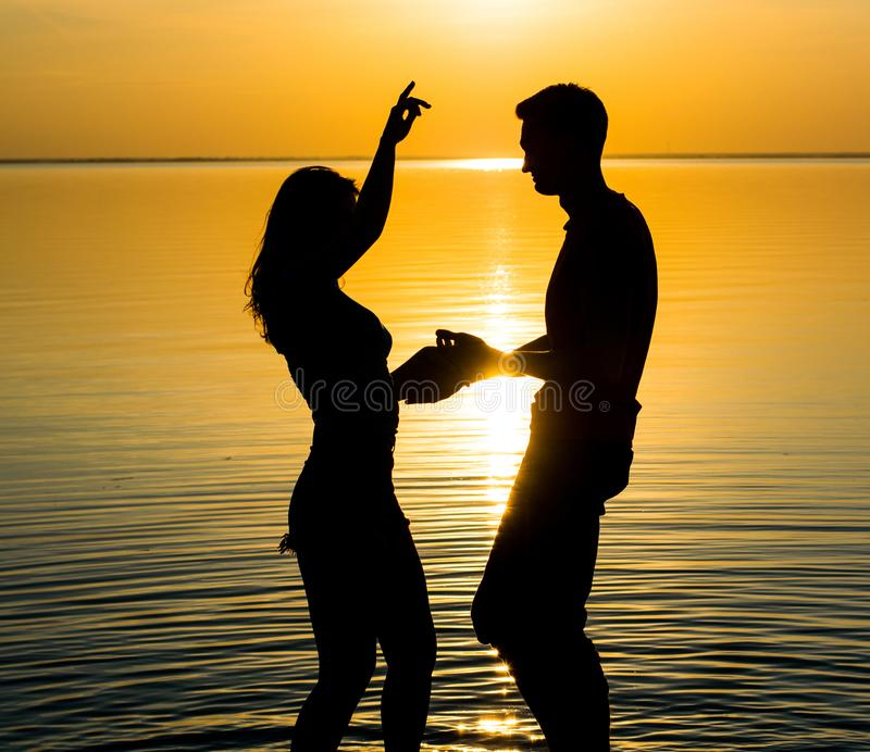 The guy and the girl are dancing at sunset background, silhouettes stock images