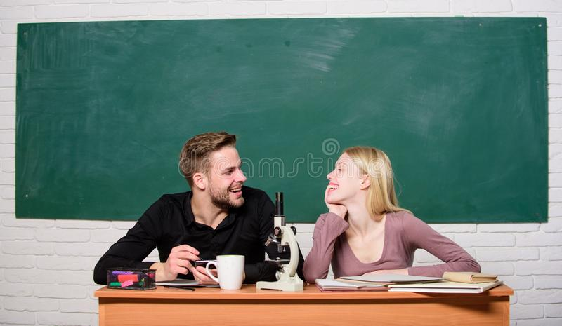 Guy and girl at desk with microscope. Studying in college or university. Biology lesson. Students studying university royalty free stock photography