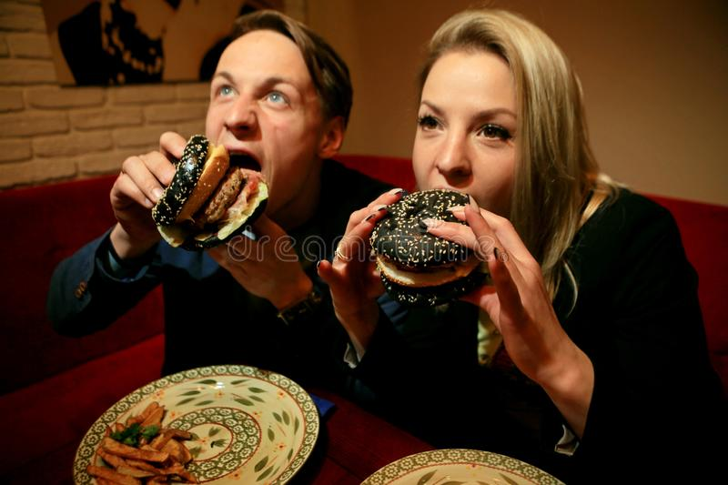 The guy and the girl eat cheeseburger with black bread, beef patty, bacon, tomatoes and pieces of cheese, dressed. With sauce and green salad, funny portrait stock image