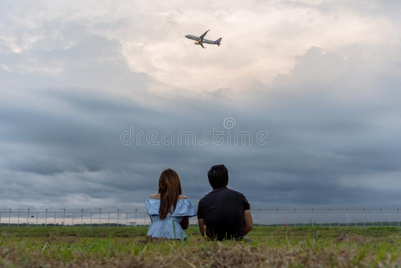 Guy and girl enjoy for looking at the plane from the green garden in the evening with blue sky cloudy and sunset time. stock photos