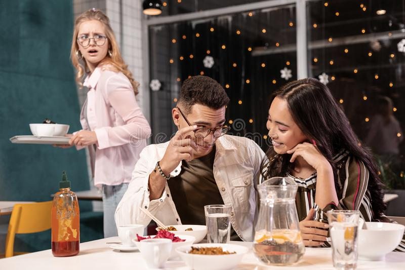 Guy and girl in glasses sitting and not noticing familiar common. Have eyes only for. Mulatto guy in glasses and brunette Asian girl sitting in cafeteria and stock photo