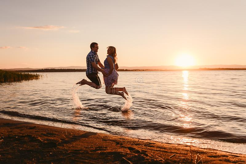 A guy and a girl jumping on sea at sunset royalty free stock image