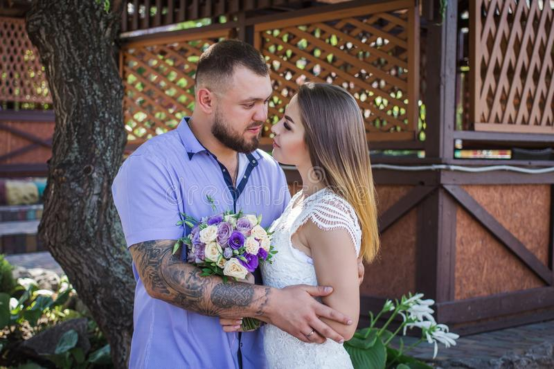 Guy and girl look at each other, portrait of a romantic couple,man and woman kissing in a dramatic light, girl holding flowers in. Guy and girl look at each stock image