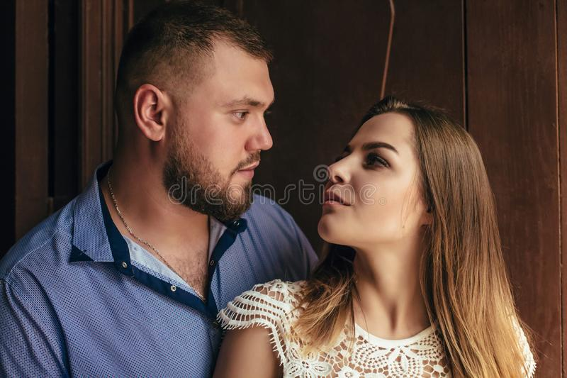 Guy and girl look at each other, portrait of a romantic couple,man and woman kissing in a dramatic light, girl holding flowers in. Guy and girl look at each royalty free stock image