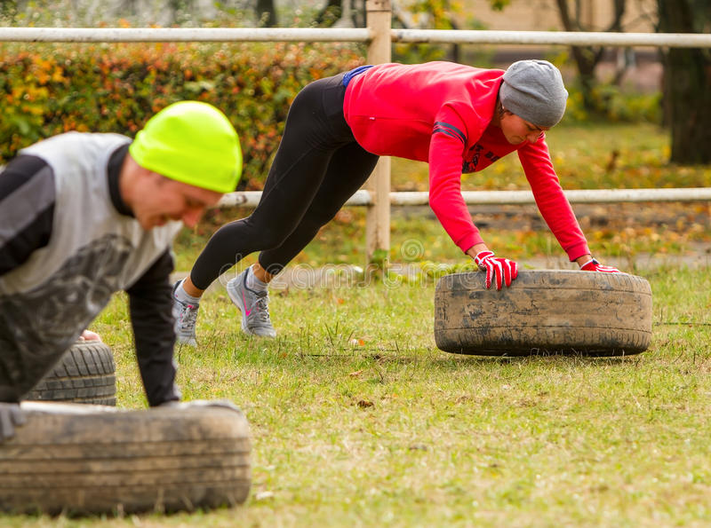 The guy and the girl perform push-ups. Kyiv, Ukraine - October 08, 2016. CrossFit training, preparation for competition `Race Nation.` Autumn. The guy and the royalty free stock photo