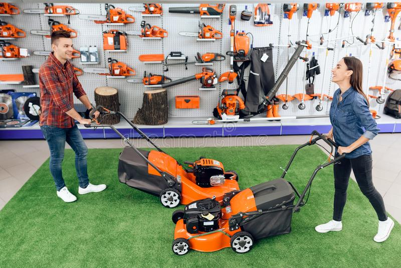 A guy and a girl are posing on the camera with a lawn mower. They came to the garden tools store. They are in a good mood. They play around royalty free stock photo