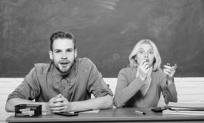 Guy and girl sit at desk in classroom. Wondering about result. Studying in college or university. Couple friends royalty free stock images