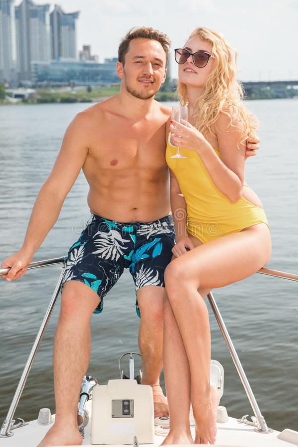 A guy with a girl is sitting on the stern of a yacht stock image