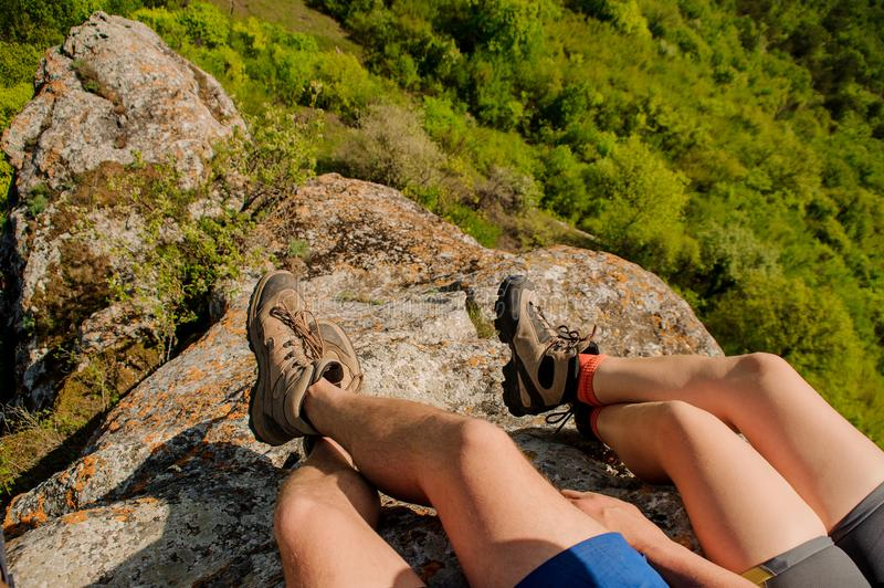 Guy and a girl in sneakers sit on a rocky mountain, dangling their legs down stock photos