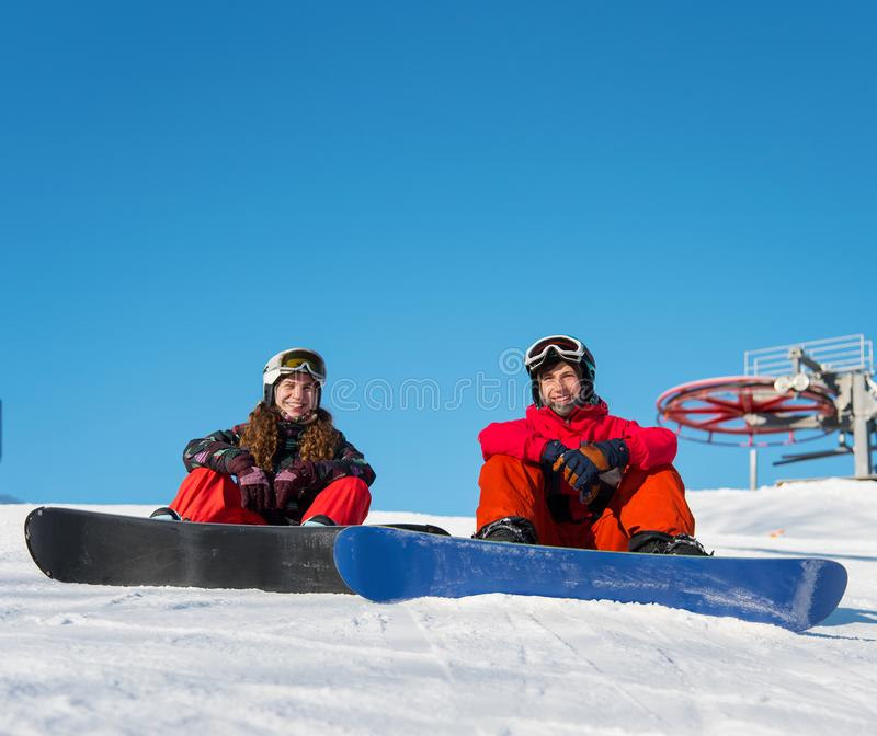 Guy and girl snowboarders are sitting on the snow at the top of the ski slope against the blue sky on a sunny day stock image