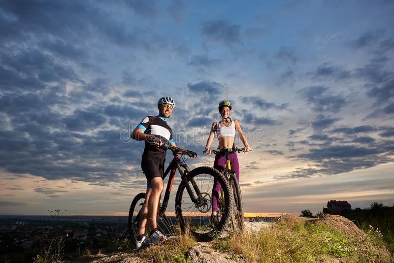 Guy and girl of sports constitution stand with bicycles on stone under beautiful cloudy evening sky stock image