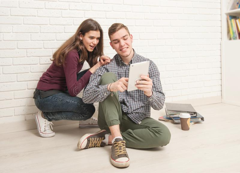 Guy and girl students sit on the floor stock image