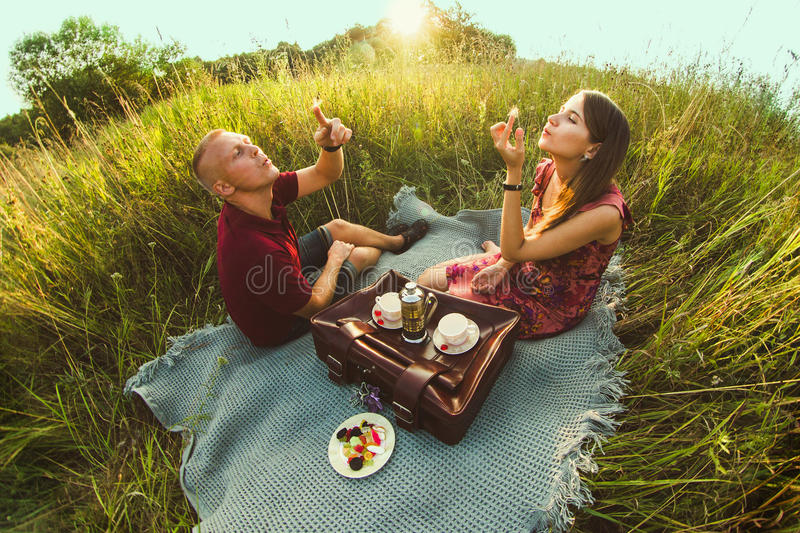Guy with a girl in summer on the grass. Drinking tea stock photography