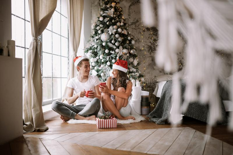 Guy and girl in white t-shirts and Santa Claus hats sit with red cups on the floor in front of the window next to the. New Year tree, gifts and candles stock images