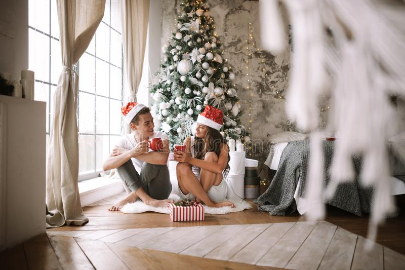 Guy and girl in white t-shirts and Santa Claus hats sit with red cups on the floor in front of the window next to the. New Year tree, gifts and candles stock photos