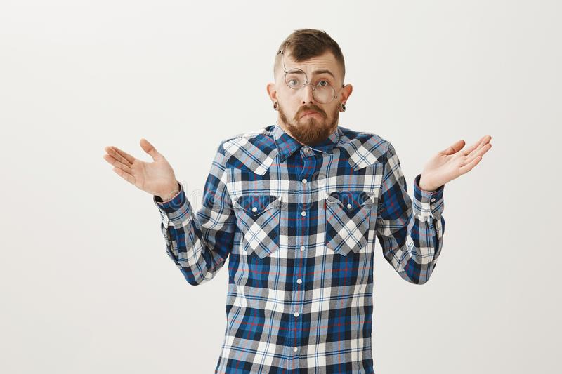 Guy give up and refuse dating after breakup. Portrait of miserable messy adult brother in blue plaid shirt and glasses. That falling from face, shrugging and stock image