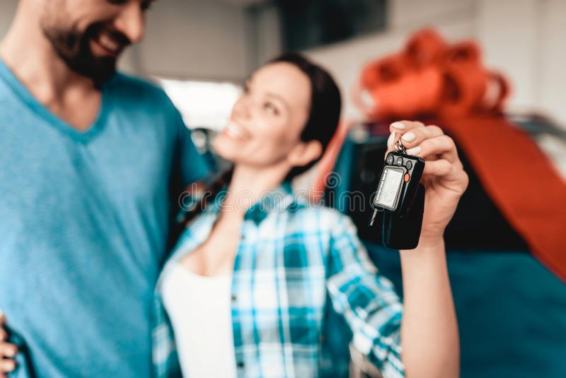 A Guy Gives A Car Key To Girlfriend. Gift Concept. A Guy Gives A Car Key To Girlfriend. Present Concept. Automobile Salon. Make A Decision. Gift Ribbon. End Of royalty free stock photos