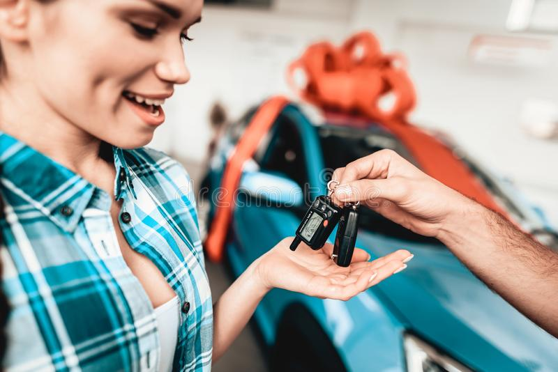 A Guy Gives A Car Key To Girlfriend. Gift Concept. A Guy Gives A Car Key To Girlfriend. Present Concept. Automobile Salon. Make A Decision. Gift Ribbon. End Of royalty free stock image