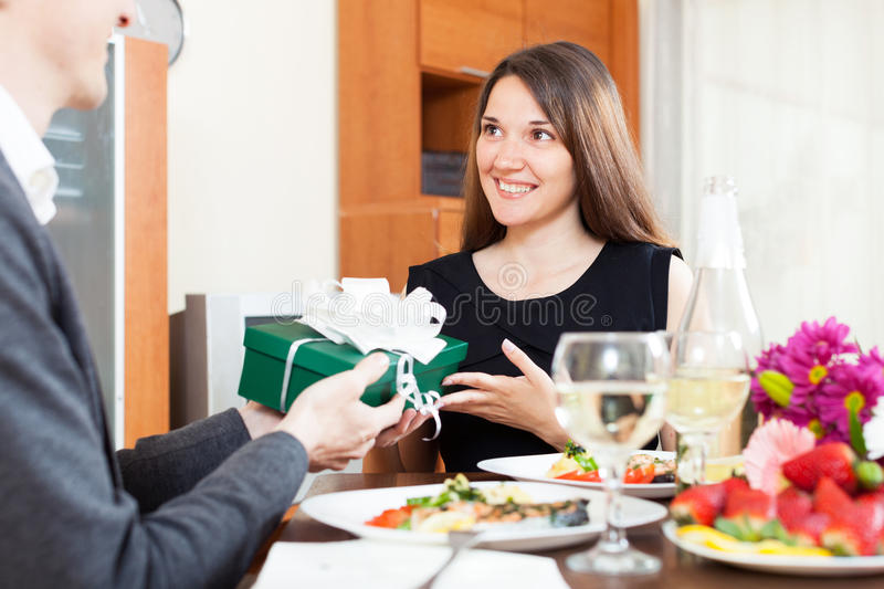 Guy gives a gift a beautiful girl. For a romantic dinner with champagne royalty free stock photo