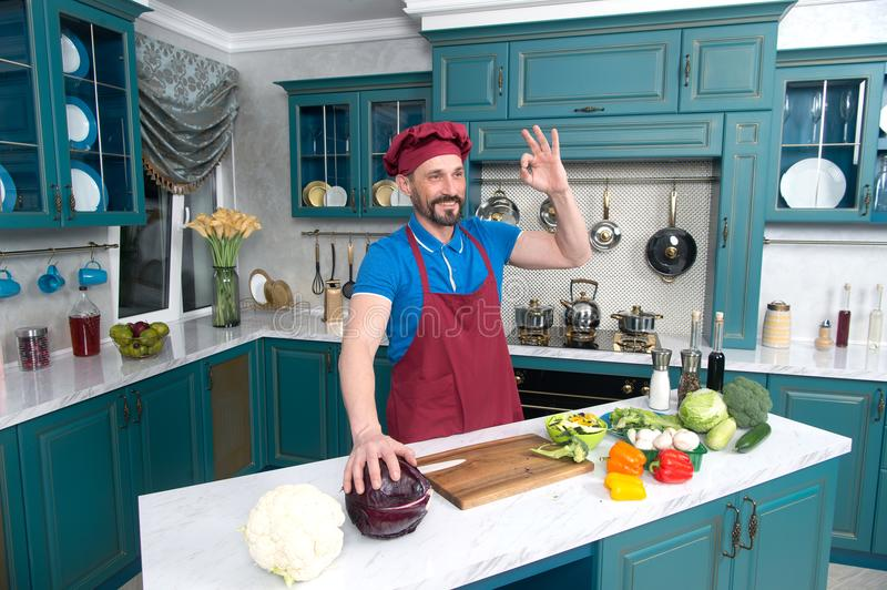 Guy gives OKey and hold red cabbage. Chef ok before cooking vegetables at kitchen. stock photos