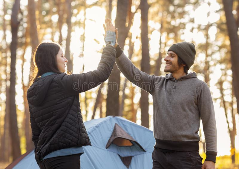 Guy giving girl high five, camping in autumn forest. Guy giving girl high five over tent in sun lights, camping in autumn forest, copy space royalty free stock photos