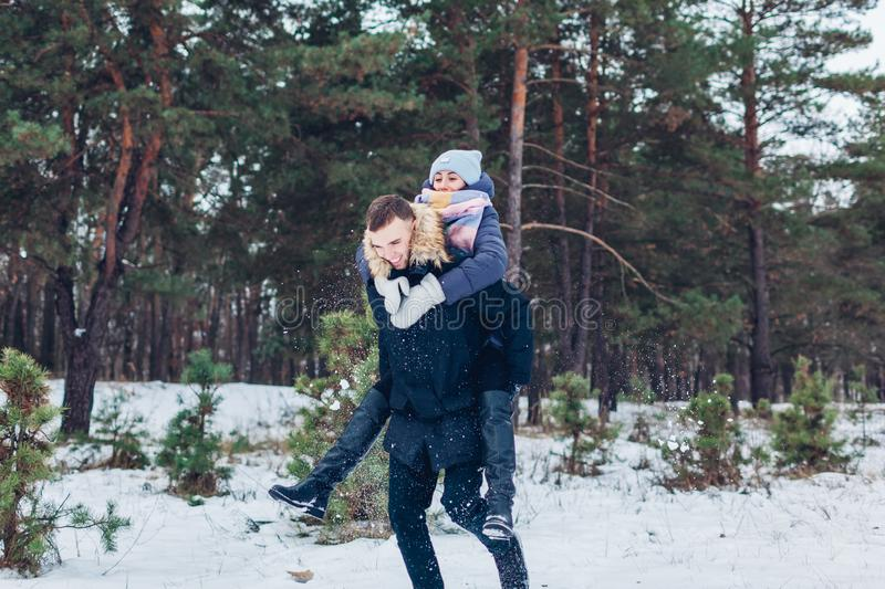 Guy giving his girlfriend piggyback in winter forest. Youn loving couple having fun outdoors royalty free stock photography