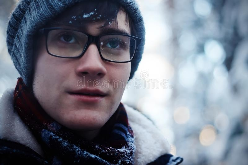 The guy with glasses and winter clothes freezes in the cold season stock photo