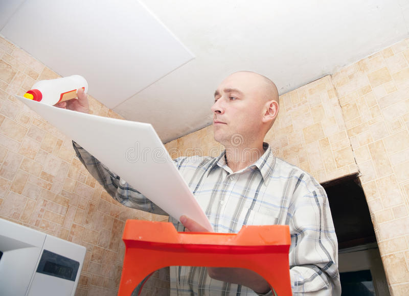 Guy glues ceiling the tile stock photography