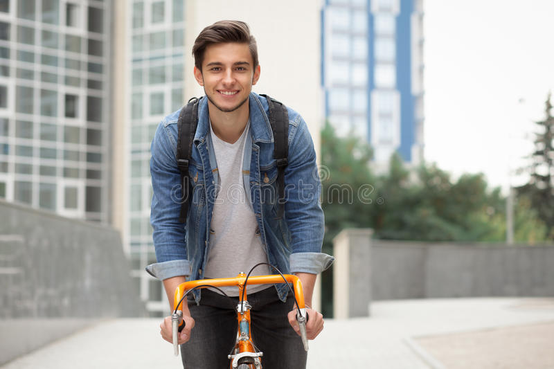 The guy goes to town on a bicycle in blue jeans jacket . young man an orange fix bike. The guy goes to town on a bicycle in a blue jeans jacket . A young man on stock photography