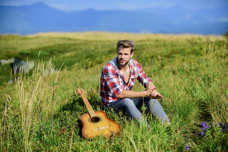 Guy with guitar contemplate nature. Inspiring nature. Pleasant time alone. Musician looking for inspiration. Dreamy. Wanderer. Wanderlust concept. Summer stock image
