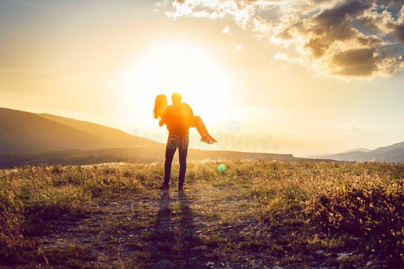 Guy Hands On His Girlfriend joven en la puesta del sol pintoresca Backgrou imagen de archivo libre de regalías