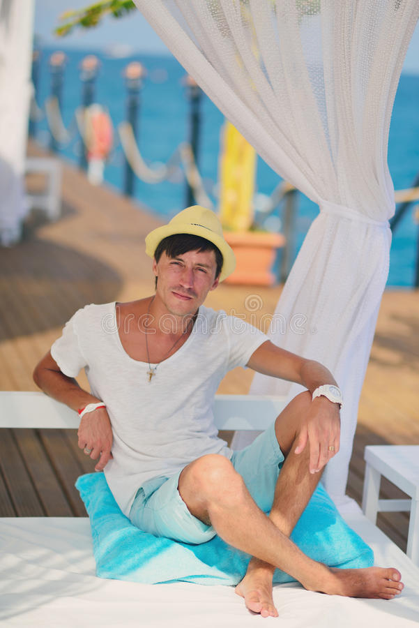 The guy in the hat under a canopy. Against the sea under a white canopy resting man in a straw hat stock image