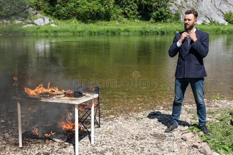 Guy hates this job. Crazy young man, hipster set fire to his desk, computer, laptop, phone. Infuriates office work stock image