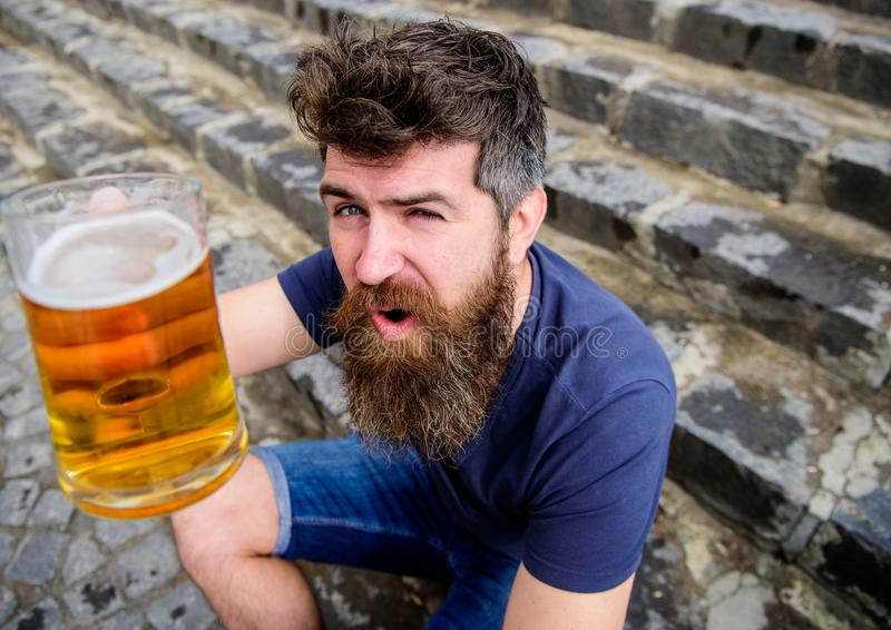 Guy having rest with cold draught beer. Hipster on cheerful face drinking beer outdoor, raising drink up. Man with beard royalty free stock photos