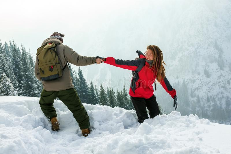 Guy helps the girl get out of the deep snow. winter trip. stock photos