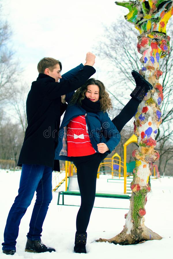 Guy helps a girl to do stretching near a tree on the street royalty free stock image