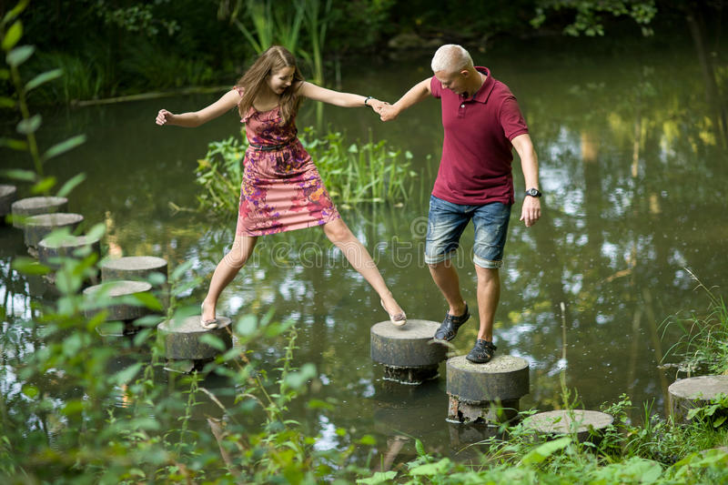 Guy helps girl. Guy helps the girl to jump the water royalty free stock photography
