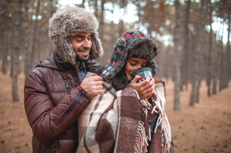 The guy hides the girl with a blanket, the girl drinks hot tea from a mug. In the autumn forest. royalty free stock photos