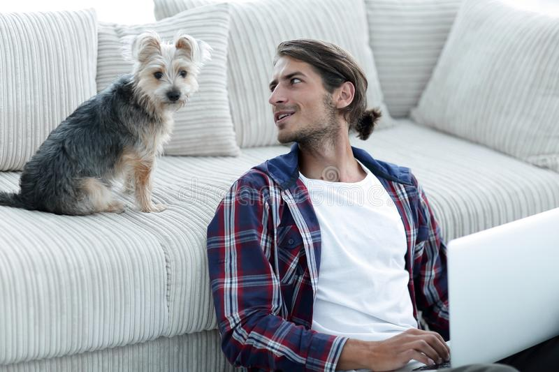 Successful guy and his favorite pet in a cozy living room. stock photography