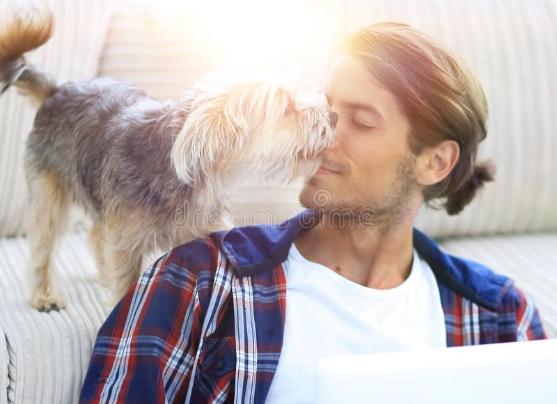 Successful guy and his favorite pet in a cozy living room. royalty free stock photo