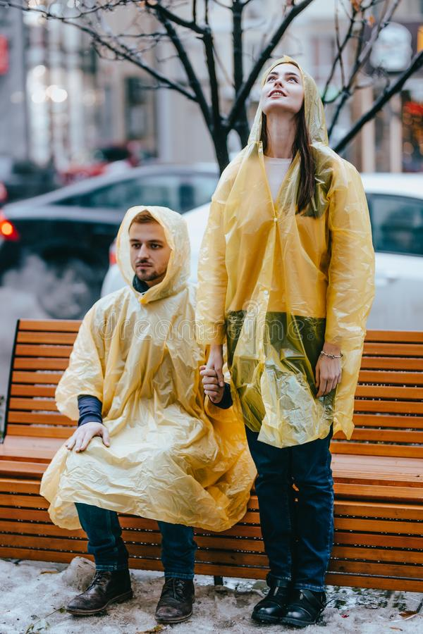 Guy and his girlfriend dressed in yellow raincoats standing near the bench on the street in the rain royalty free stock photography